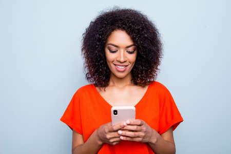Porträt der beschäftigten charmanten Frau mit der modernen Frisur im lebendigen Outfit, das Smartphone in den Händen unter Verwendung des Wi-Fi 3G-Internets hält, das E-Mail-Suchkontakt lokalisiert auf grauem Hintergrund prüft