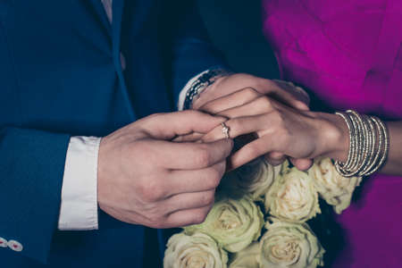 Cropped close up portrait of trendy rich gentleman mr in suit putting on engagement ring accessories on finger to lady mrs having white roses hands, lovely romantic couple isolated on grey background Stock Photo
