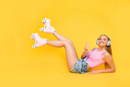 Portrait of friendly joyful girl lying on floor ground with raised legs wearing roller skates gesturing v-sign peace symbol isolated on yellow background using headset