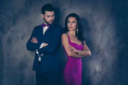 He vs she! Portrait of couple standing back to back holding arms crossed looking at each other isolated on grey background, pretty hispanic latin lady in tight purple dress gentleman in tux with bow Stockfoto