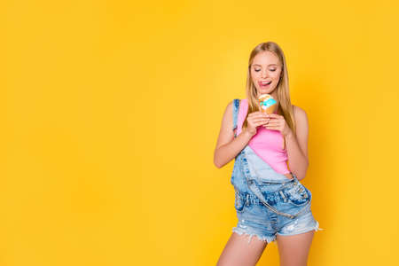 Portrait of tempting girl licking her upper lip looking at vanilla caramel ice cream in waffle cone in hands isolated on yellow background, good summer vibes only concept