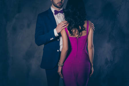 Cropped portrait rear view of pretty brunette woman with curly hair in violet apparel harsh half face man in tuxedo bowtie holding hands shoulders  lover mysterious couple isolated on grey background Imagens