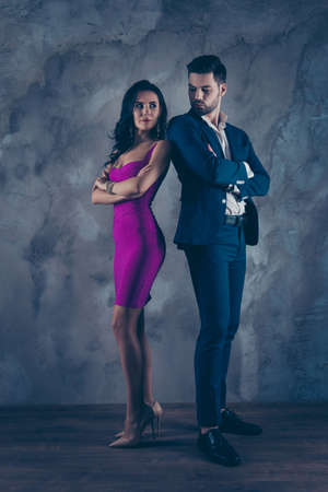 Full size fullbody vertical portrait of attractive confident couple with crossed arms looking at each other, charming slim lady in purple tight dress gentlemen in tuxedo isolated on grey wall