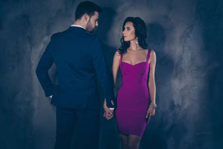 Rear view portrait of brunet mr in tux and pretty mrs with front view in purple tight dress with hairstyle tempting decollete, spouses looking at each other holding hands isolated on grey background Stock Photo