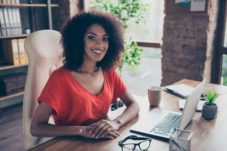 Portrait of trendy charming attorney with beaming smile in casual outfit sitting at desk in modern office looking at camera. People person profession vector concept Stockfoto