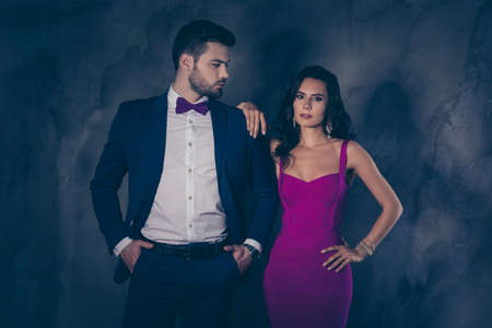 Profile portrait of virile cool mr in blue tux with bow holding two hands in pants looking at his charming brunette mrs with jewerly in lilac dress isolated on dark grey background
