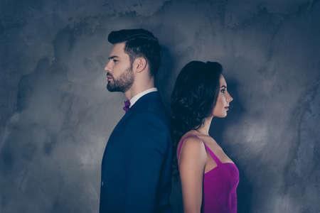 ¡Los opuestos se atraen! ¡Él contra ella! Retrato de perfil de pareja atractiva peinado de pie espalda con espalda aislado sobre fondo gris, bonita dama morena en traje púrpura caballero en esmoquin arco de cerdas