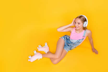 Portrait of pleased girl using headphones listening favorite music wearing roller skates having pleasure enjoyment delight free time daydream isolated on yellow background, looking away Imagens