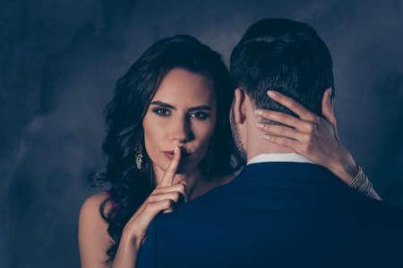 Shh! Portret van verleidelijke brunette dame stilte teken tonen met wijsvinger aanraken van geheime mysterieuze heren met zicht naar achteren, mooie heer en mevrouw geïsoleerd op een grijze achtergrond