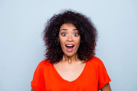 Portrait of shocked amazed woman with modern hairdo in orange bright outfit keeping wide open mouth isolated on grey background