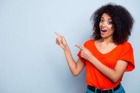 OMG! Portrait of astonished amazed woman with wide open mouth gesturing copy-space with two forefingers looking at camera isolated on grey background