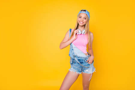 Portrait of pretty charming girl in cap with headset on neck holding hand in pocket of denim shorts looking at camera isolated on yellow background, pleasure delight enjoyment concept Stock Photo