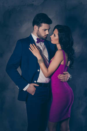 Portrait of bearded man in tuxedo with bow holding hand in pocket of pants and charming pretty lady with booty ass jewelry, attractive spouses hugging looking at each other over grey background