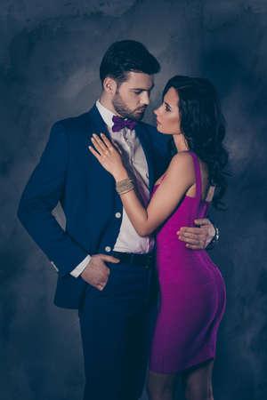 Retrato de hombre barbudo en esmoquin con lazo sosteniendo la mano en el bolsillo de los pantalones y encantadora dama bonita con joyas de botín, esposas atractivas abrazándose mirando el uno al otro sobre fondo gris