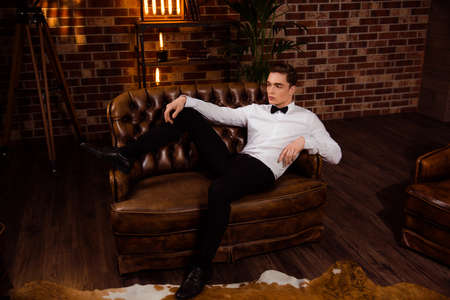 Manly, virile, dreamy man formal wear with bow laying on leather sofa over brick wall in interior room, with thoughtful expression looking to the side