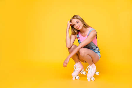 Portrait with copyspace empty place of pretty gorgeous girl on roller skates sitting looking at camera isolated on yellow background 写真素材