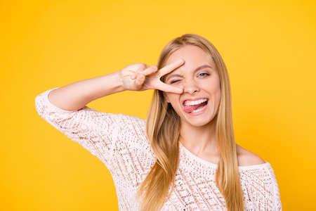 Porträt des törichten verspielten Mädchens gestikulierendes V-Zeichen nahe dem zwinkernden Auge, das Zunge heraus schaut, die Kamera betrachtet, die verrückte Stimmung lokalisiert auf gelbem Hintergrund hat