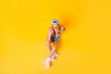 Top view portrait of funky positive girl looking out glasses on face sitting on floor ground isolated on yellow background, wellness fitness athletic workout concept