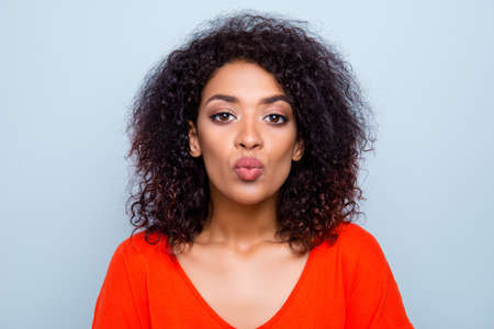 Portrait of pretty trendy woman in bright outfit blowing air kiss with pout lips isolated on grey background. Augmentation concept Stock Photo