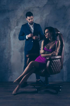 Portrait of sexual hot woman in purple dress sitting in leather chair trendy man unbutton jacket looking at bitch having erection lovely attractive couple isolated on grey dark background