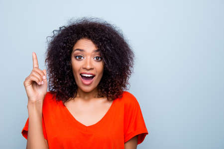 Portrait of amazed funny woman with modern hairdo in vivid outfit gesturing forefinger up with wide open mouth eyes having good idea isolated on grey background