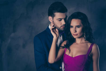 Portrait of pretty charming woman with curly hair decollete virile harsh man with stubble embracing hugging having serious expression isolated on grey background with copy space empty place