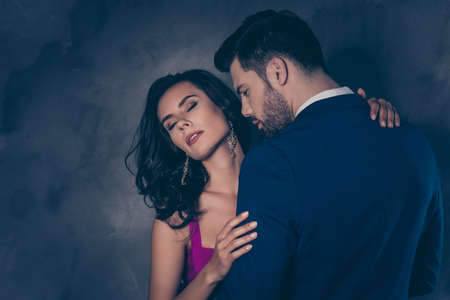Portrait of seductive brunette lady with close eyes enjoying gentle touch of gentlemen with stubble, lovely mr and mrs isolated on grey background, true feelings perfume aroma neck concept