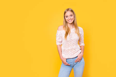 Portrait of charming trendy girl in casual outfit with naked shoulder looking at camera holding two hands in pocket of jeans isolated on bright vivid yellow background
