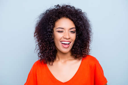 Portrait of cheerful joyful woman in orange outfit with modern hairdo winking with one eye looking at camera isolated on grey background. Affection dream feelings concept
