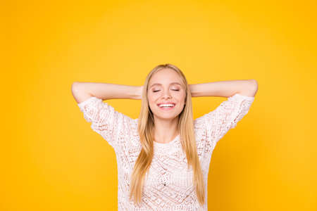 Portrait of cheerful cute girl holding hands behind head keeping eyes closed remembering funny moments isolated on yellow background