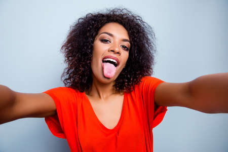 Self portrait of funky modern woman in vivid outfit shooting selfie on front camera gesturing tongue out isolated on grey background. Photography concept