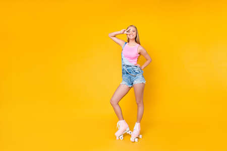 Full size body portrait of pretty funky girl on roller skates gesturing v-sign near eye looking at camera isolated standing over yellow background