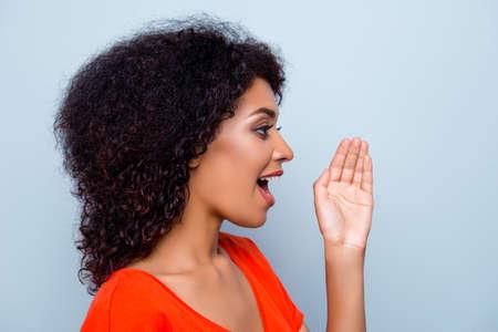 Hallo du! Porträt der hübschen verantwortungsbewussten Frau mit der modernen Frisur, die Handfläche nahe weit offenem Mund hält, der jemanden anruft, der Informationsansage laut auf grauem Hintergrund schreit Standard-Bild