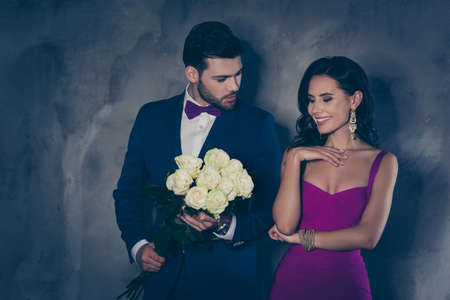 Portrait of charming mrs in dress decollete attractive mr in tuxedo with bow holding bouquet of white roses prepare surprise, lovely romantic spouses isolated on grey background. Wedding special day