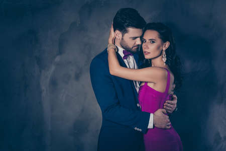 Portrait of lovely romantic couple embracing, pretty mrs jewelry, rich harsh mr with bristle in tux with bowtie enjoying smell of lover isolated on grey background. Betrayal adultery perfume concept