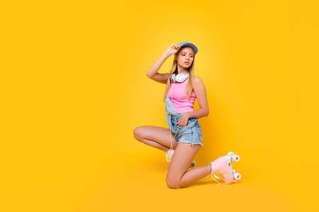 Porträt des hübschen bezaubernden Mädchens in Jeans insgesamt mit Headset am Hals, das Hand in der Tasche der Shorts hält, die zurück schaut, die auf einem Knie lokalisiert auf gelbem Hintergrund aufwirft Standard-Bild
