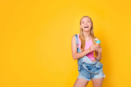 Portrait with copy space empty place of funny comic girl sincere laughing having caramel vanilla ice cream scoops in cone in hands enjoying daydream isolated on yellow background