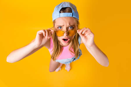 WTF! Top view portrait of sad disappointed girl looking out glasses on face holding eyelets with two hands isolated on yellow background