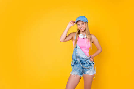 Portrait with copyspace empty place of cheerful charming girl in cap with headset on neck  isolated on yellow background, pleasure delight enjoyment advertisement concept