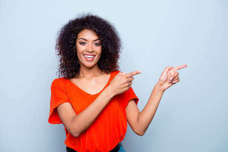 Portrait of cheerful toothy woman with modern hairdo plump lips in vivid outfit gesturing copyspace with two forefingers looking at camera isolated on grey background Stockfoto