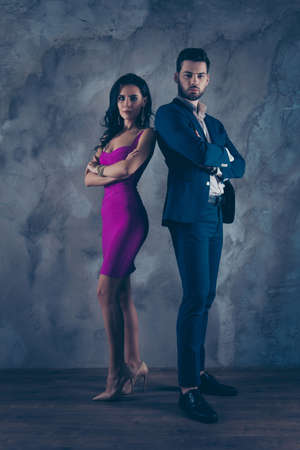 Opposites attract! Full size fullbody vertical portrait of attractive, confident couple with crossed arms looking at camera pretty slim lady purple tight dress gentlemen in tux standing over grey wall