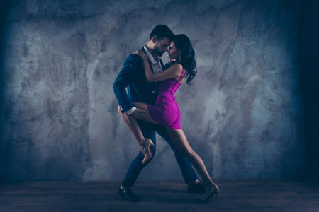 Full size fullbody portrait of romantic lovely couple, pretty lady in purple tight dress gentlemen in tuxedo, face to face standing close in tango position, isolated on concrete background