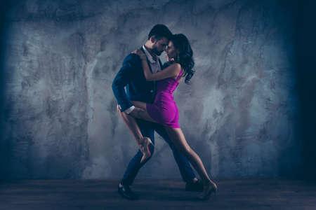 Retrato de cuerpo entero de tamaño completo de una pareja romántica encantadora, dama bonita en caballeros de vestido ajustado morado en esmoquin, cara a cara de pie cerca en posición de tango, aislado sobre fondo de hormigón Foto de archivo