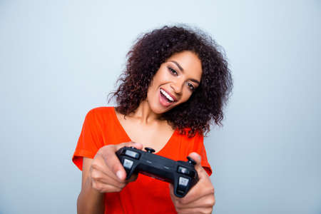 Portrait of funny playful woman with modern hairdo using joystick playing video game enjoying free time isolated on grey background