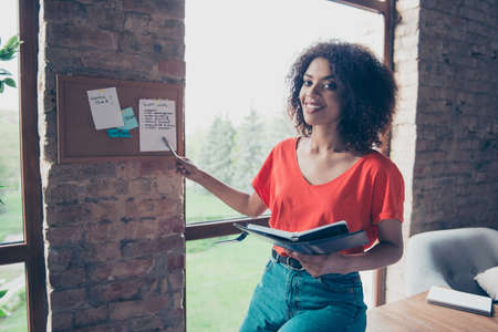 Portrait of pretty trendy woman in jeans bright t-shirt holding organizer in hand showing message on sticky pinning on board with pencil looking at camera. Study education university concept