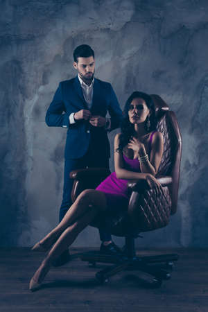 Portrait of sexual hot woman in purple dress sitting in leather chair looking at camera trendy man unbutton jacket looking at bitch having erection couple isolated on grey dark background