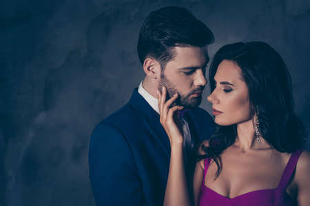 Portrait of naughty romantic couple looking at each other gentle touch, pretty charming brunette lady harsh bearded hispanic gentlemen isolated on grey background with copy space. Intimacy concept