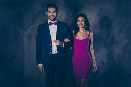 Portrait of positive cheerful lady with hairstyle curls and positive man with bristle in blue tuxedo famous lovely couple looking at camera isolated on dark grey background with shadow