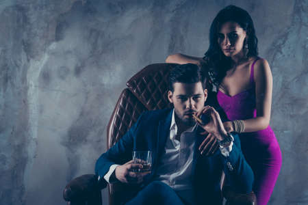 Portrait of brutal gentleman in formal wear sitting in leather chair holding glass with whiskey cigar in hands, charming pretty lady standing near looking at camera isolated on grey background Imagens