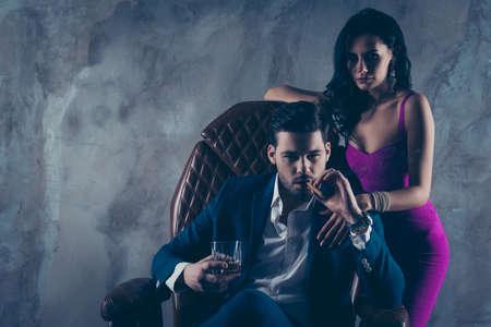 Retrato de caballero brutal en ropa formal sentado en una silla de cuero con vaso con cigarro whisky en las manos, encantadora dama bonita de pie cerca mirando a cámara aislada sobre fondo gris Foto de archivo